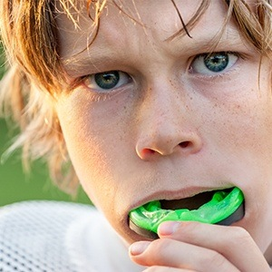 Teen boy placing green sportsguard