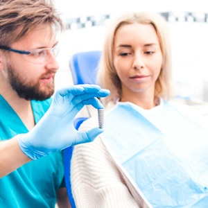 A dentist showing a female patient an actual dental implant and explaining how it is placed