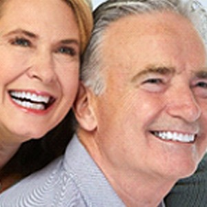 A happy older couple smiling and showing off their new dental implants