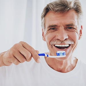 Smiling man brushing teeth