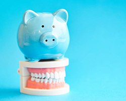 piggy bank and model teeth demonstrating cost of dental implants in Alhambra