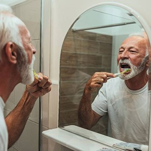 man brushing his teeth to care for dental implants in Alhambra