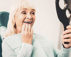 woman admiring her new dental implants in Alhambra