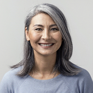 A middle-aged woman with pepper gray hair smiling to show off her new dental implants
