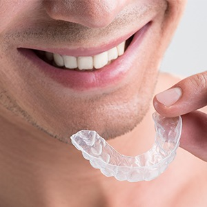 Closeup of smiling man holding Invisalign tray