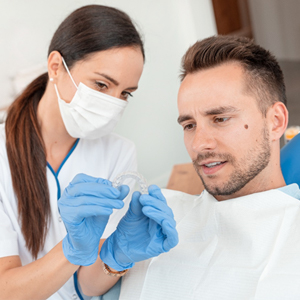 A dentist showing a male patient how an Invisalign aligner works