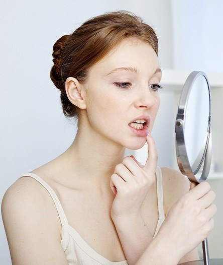 Woman looking at irritatd gums in  mirror