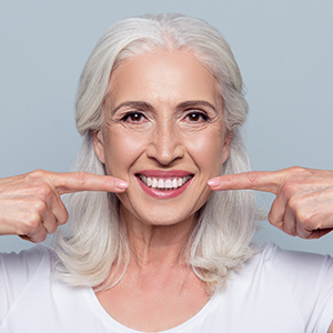 Woman pointing to healthy smile